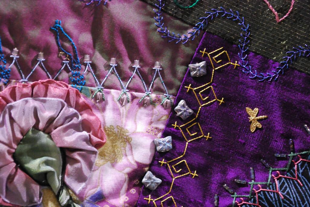 Closeup of a crazy quilt's elegant fabrics and  stitching.