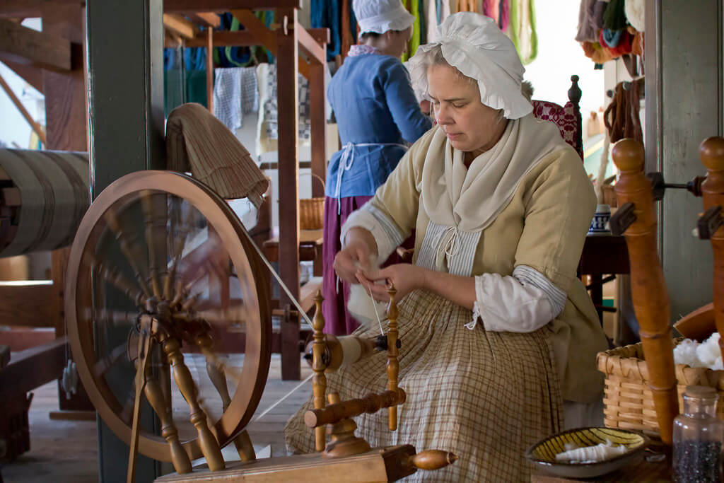 Colonial woman at spinning wheel
