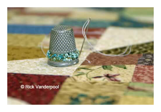 Pretty thimble with threaded needle